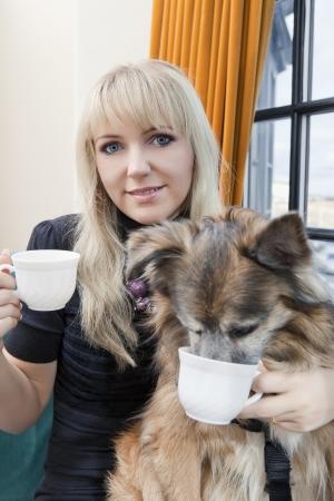 likeness: Beautiful woman and her dog having their tea