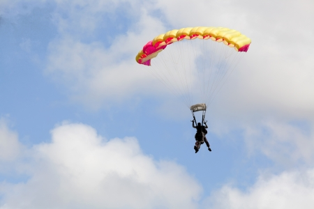 skydive: Tandem of skydivers with a colourful  parachute