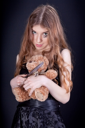 young knife: Beautiful violent girl destroying toy Stock Photo