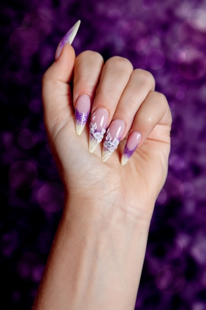 Female hand with beautiful purple manicure photo