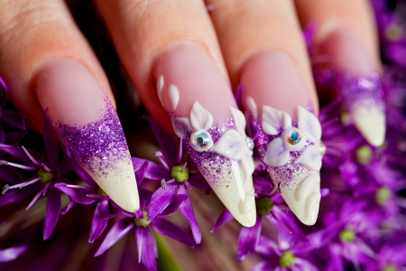 Close-up of female beuatifully manicured nails in purple