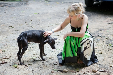 Woman giving comfor to a poor homeless dog