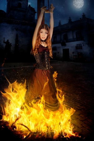 Beautiful young witch in the flames of fire Stock Photo