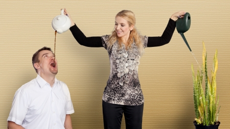 Multitasking housewife watering plant and providing husband with a coffee Stock Photo - 18118875