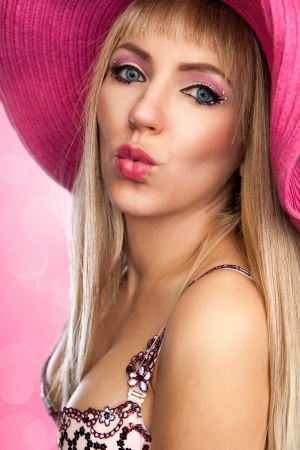 Blond beauty in a pink hat photo
