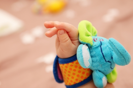 Baby hand with elephant toy Stock Photo