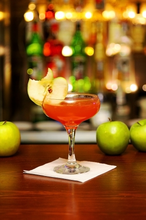 Red cocktail with piece of apple standing on bar counter