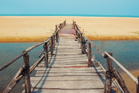 far away: Creative travel photo with blue sky, sea, beach and wood plank road leading far away