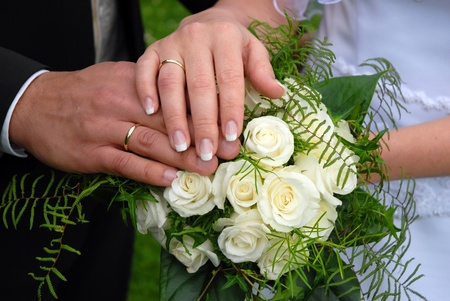 ring finger: Wedding rings on wedding day,against the background of a wedding bouquet.