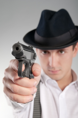 gangster background: Dangerous gangster in hat holds a pistol and aims
