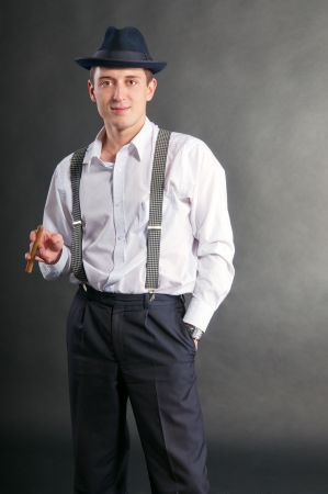 young gangster man with cigare on gray background photo