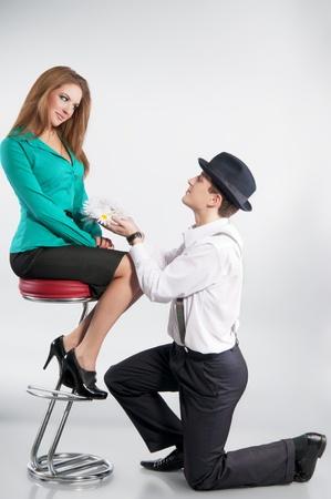 mujer arrodillada: Feliz hombre joven guapo entregando un flores a una joven y bella mujer. Sobre un fondo gris