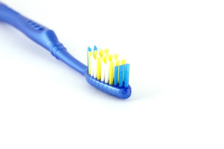 Tooth-brush with blue handle over white. Shallow DOF.