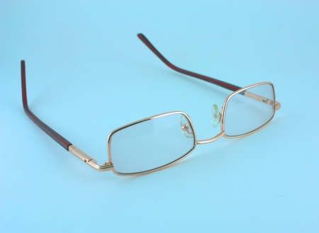 Golden optical glasses isolated on blue