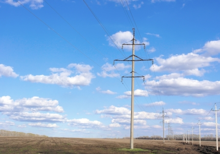 Power line of electricity transmissions on the field
