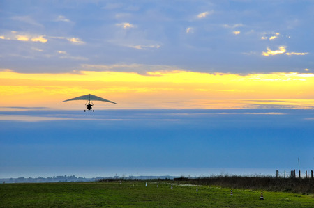 pilotage: motor hang glider in the cloudy sunset Stock Photo