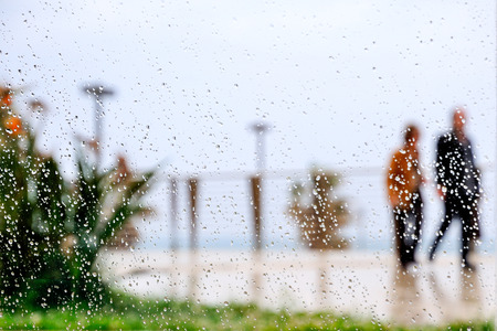 rain drop on glass with older people blurred