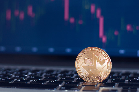 Golden Monero in front of laptop with stock exchange graph background. Digital money concept. Stock Photo