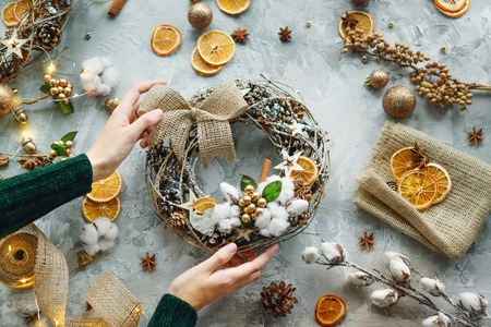 Christmas background with decorations and women hands, wreath, oranges, cardamom. Top view. Flat lay. Copy space. 版權商用圖片