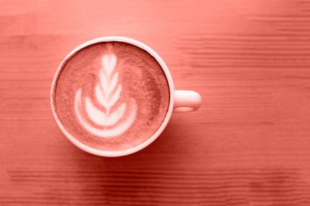 Cup of Living Coral cappuccino on wooden background. Color of the year 2019 concept. Cup of cappuccino with latte art on wooden table.