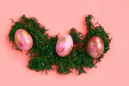 Pink Easter eggs with golden strokes on grass and coral background. Creative concept.