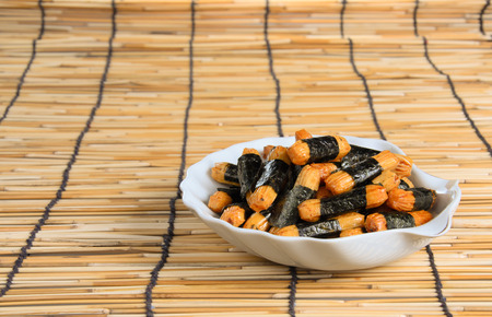 alga: Japanese crispy snack wrapped with salted alga , put in a plate on a bamboo mat
