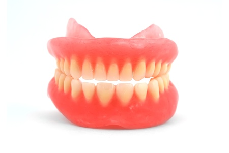 Plastic dentures on a white background photo