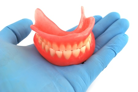 dentures in his hand on a white background