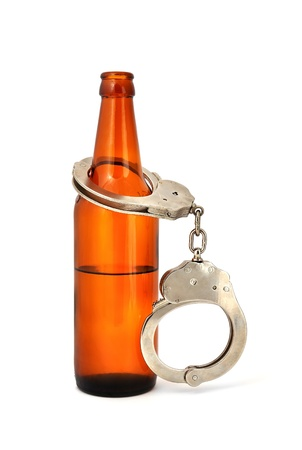 handcuffs and  bottle on a white background photo