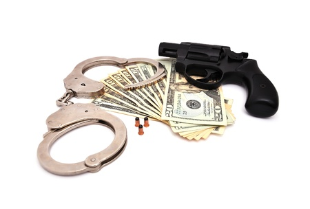 revolver,  dollars and the handcuffs on a white background Stock Photo - 9729874