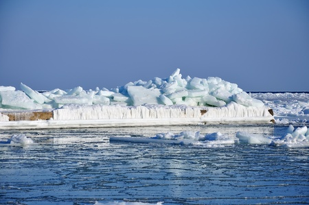 Pierce frozen in ice at sea and blue sky photo