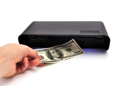dinero falso: Detector de billetes y el dinero en el fondo blanco Foto de archivo