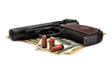 pistol, cartridges and dollars on a white background Фото со стока