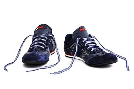 untied: zapatillas de deporte con cordones desatados sobre un fondo blanco Foto de archivo