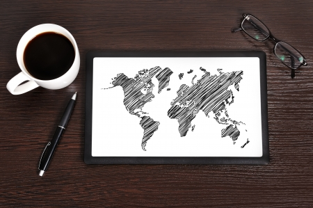 Workplace with world map on touchpad photo