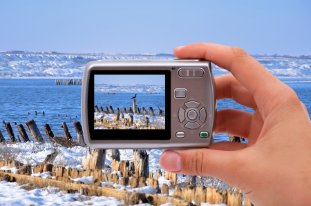 camera in hand of photographing ice pier photo