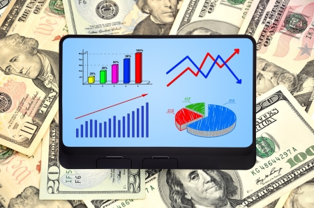 digital tablet with scheme growth profits on background of dollars photo