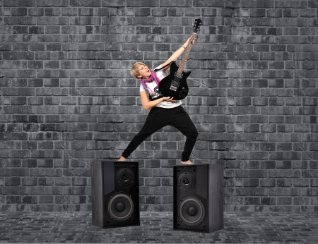 girl with guitar and speakers on brick background photo