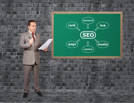 businessman with paper and scheme seo in brick room Stock Photo - 17576874