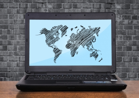 laptop with world map on monitor photo