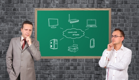 two businessman dreaming and computer network on blackboard photo