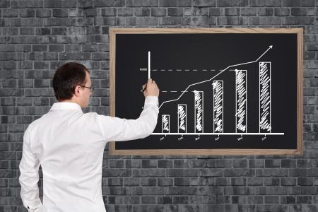 businessman drawing business chart on blackboard Фото со стока