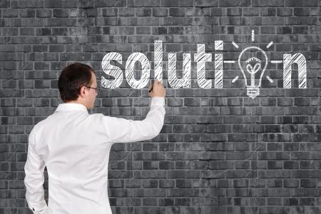 businessman drawing solution symbol on brick wall photo