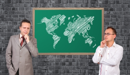 two businessman and world map on blackboard photo
