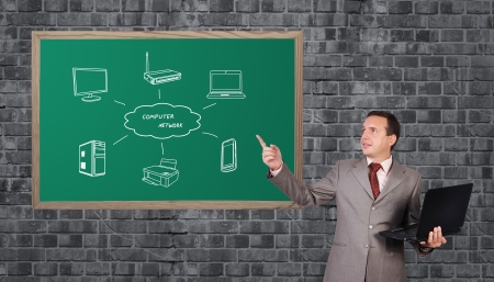 businessman with a laptop pointing to wireless scheme on blackboard photo