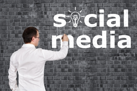businessman drawing social media on brick wall photo