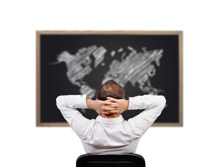 man looking on blackboard with world map photo