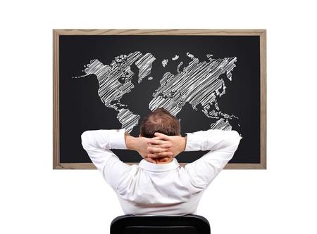 man looking on blackboard with world map photo