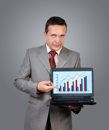 businessman with laptop in hand points to chart of profits photo