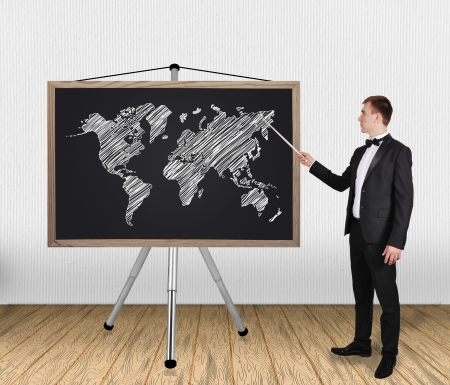 businessman in tuxedo pointing at world map on blackboard photo